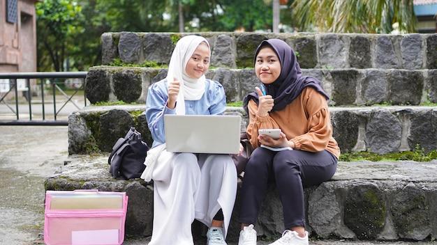 Duas amigas estudantes asiáticas discutindo com um gesto de aprovação