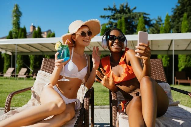 Duas amigas fazendo selfie em espreguiçadeiras na piscina