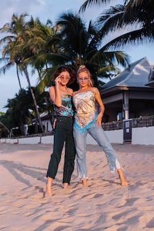Duas amigas felizes com óculos de sol de férias em um país tropical