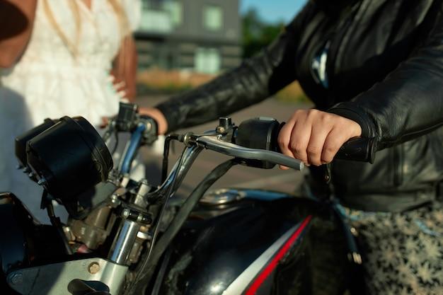 Duas amigas ficam perto de uma moto. vender o conceito de motocicleta na cidade.