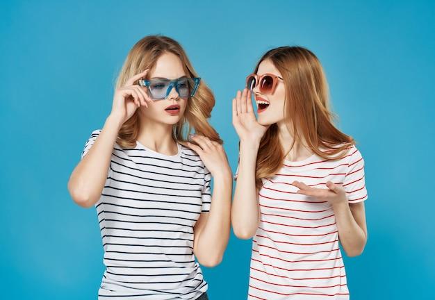 Duas amigas fofas, moda verão, diversão, abraçam fundo azul