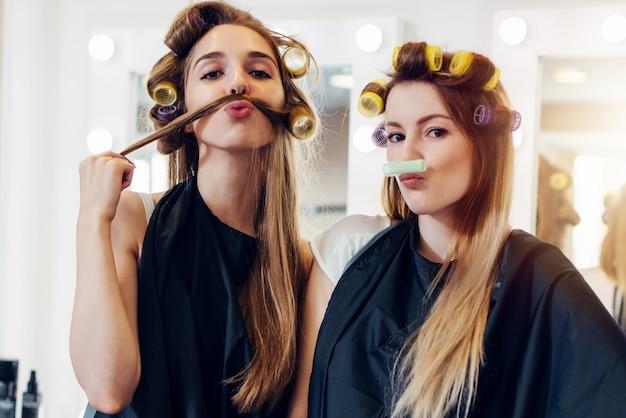 Duas amigas fofas na capa preta usando rolinhos fazendo bigode do cabelo e rolo no salão de cabeleireiro
