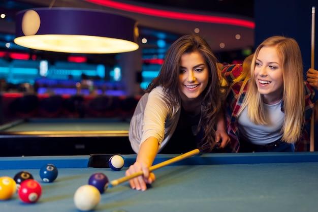 Duas amigas jogando sinuca