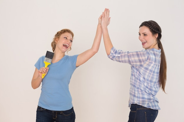 Duas amigas jovens e alegres que dão alta cinco