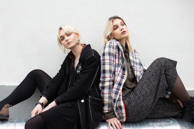 Duas amigas jovens e elegantes loiras em jaquetas grandes e elegantes com botas de couro da moda sentadas em um cachimbo de prata vintage perto da parede na rua