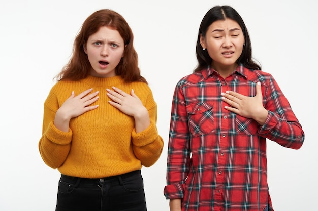 Duas amigas jovens e infelizes. confuso, apontando duvidoso de si mesmo. conceito de pessoas. vestindo um suéter amarelo e camisa xadrez. isolado sobre a parede branca