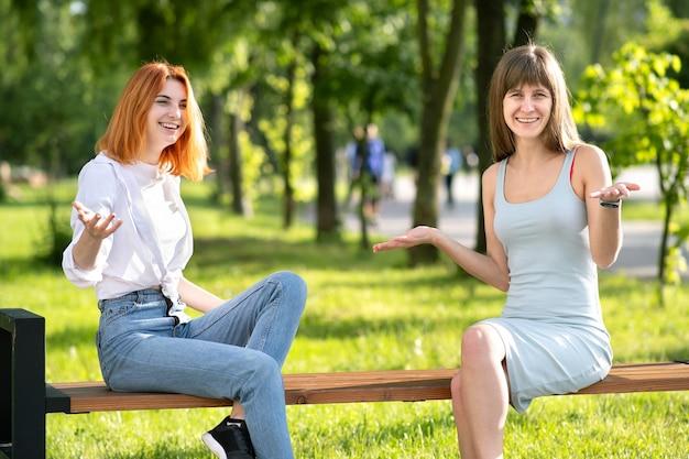 Duas amigas jovens sentadas em um banco no parque de verão conversando alegremente e se divertindo