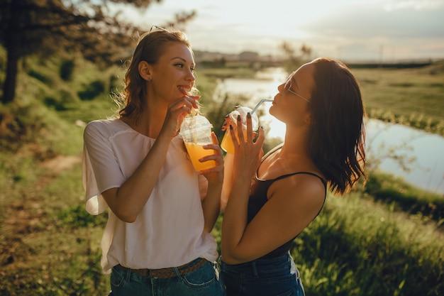 Duas amigas legal se divertem no verão, beber um cocktail, ao pôr do sol, expressão facial positiva, ao ar livre