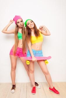Duas amigas lindas e felizes com seu skate