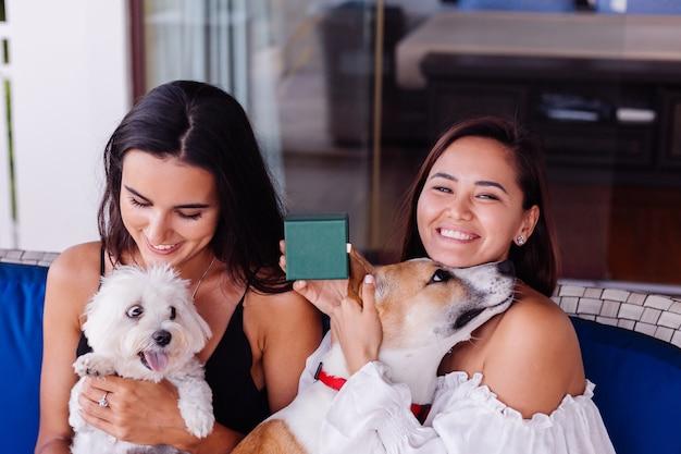 Duas amigas lindas e felizes relaxando em casa no sofá, sorrindo e brincando com cachorros