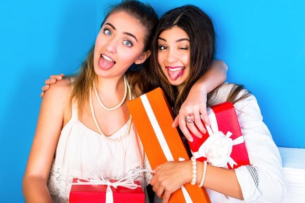 Duas amigas lindas segurando brilhantes presentes de natal