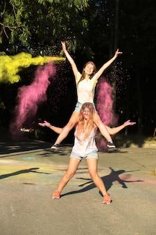 Duas amigas loiras felizes se divertindo com a explosão do pó de holi