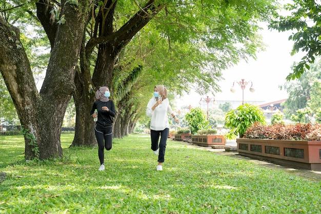 Duas amigas muçulmanas correndo juntas e usando uma máscara