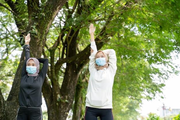 Duas amigas muçulmanas felizes fazendo exercícios juntas e usando uma máscara