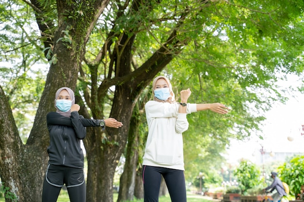 Duas amigas muçulmanas se exercitam juntas e usam uma máscara