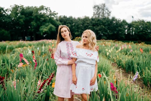 Duas amigas muito jovens em vestidos étnicos relaxantes no jardim no verão. pares de mulheres descalças bonitos nos bordados do país que guardam as mãos e que abraçam exteriores. menina na moda elegante