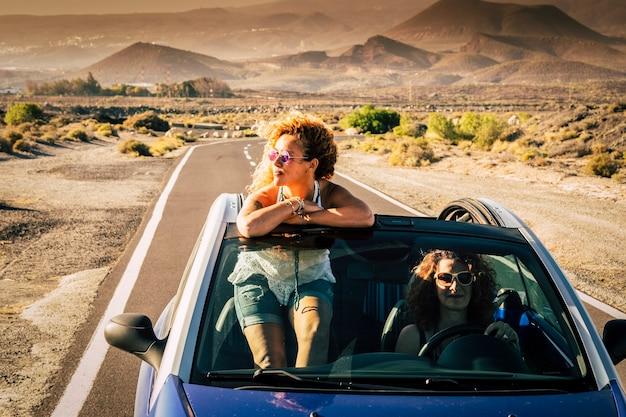 Duas amigas mulheres adultas viajando juntas livres e independentes em um carro convergente com montarias e um deserto de natureza selvagem em cena