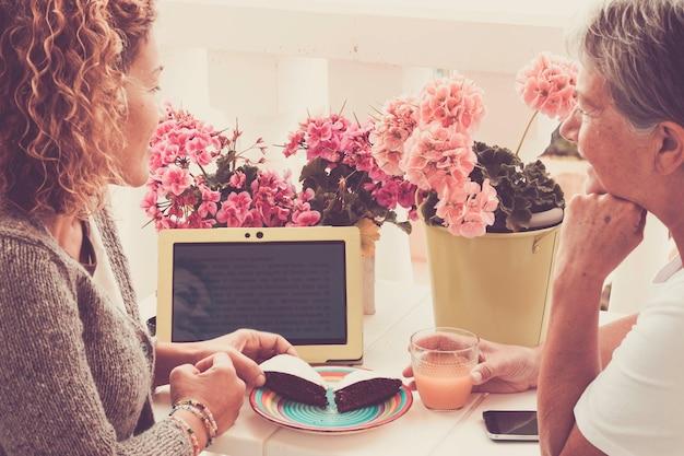 Duas amigas, mulheres de meia e terceira idade de 40 e 70 anos, ficam juntas em uma feliz tarde de lazer comendo um bolo e bebendo frutas lendo algo no laptop e um celular na mesa