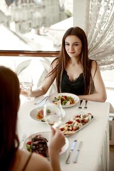Duas amigas mulheres estão comendo no restaurante e dizendo torradas