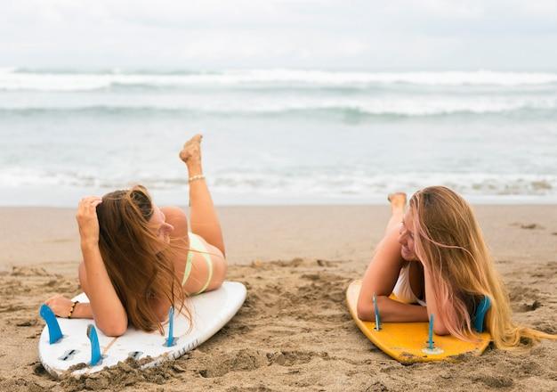 Duas amigas na praia subindo em pranchas de surf