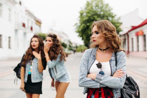 Duas amigas no fundo fofocando sobre terceiro adolescente com maquiagem e penteado, olhando para longe com tristeza.