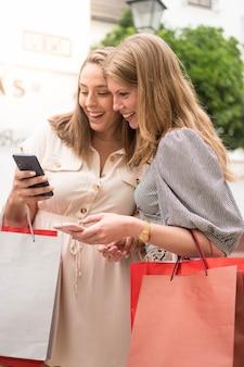 Duas amigas olhando para o celular rindo na rua depois de fazer compras na rua