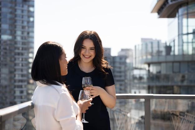 Duas amigas passando um tempo juntas bebendo vinho em um terraço na cobertura
