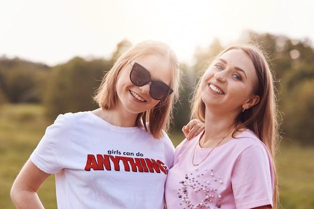 Duas amigas positivas usam camiseta e tons