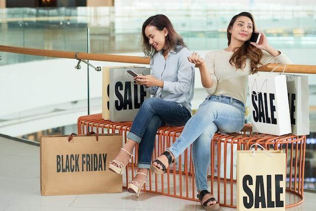 Duas amigas relaxantes após compras bem-sucedidas com seus smartphones