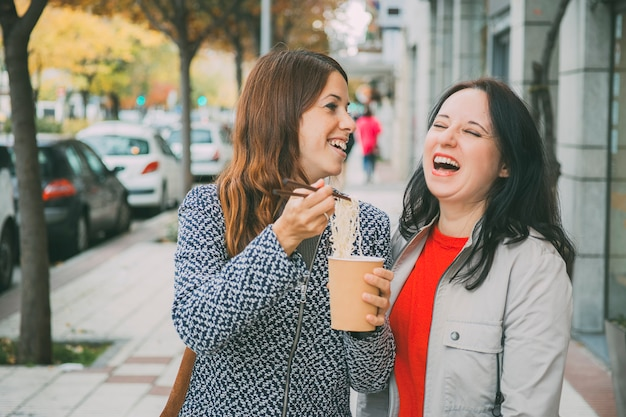 Duas amigas rindo na rua comendo comida chinesa