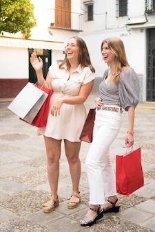 Duas amigas rindo na rua depois de fazer compras na rua duas mulheres felizes