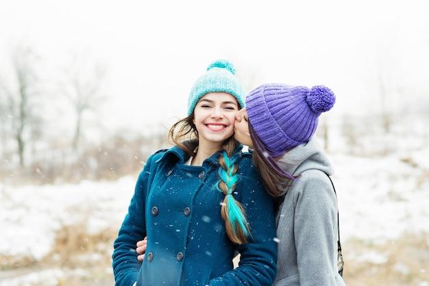 Duas amigas se abraçando e se beijando ao ar livre em um dia nevado de inverno