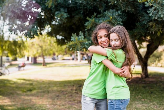 Duas amigas se abraçando no jardim