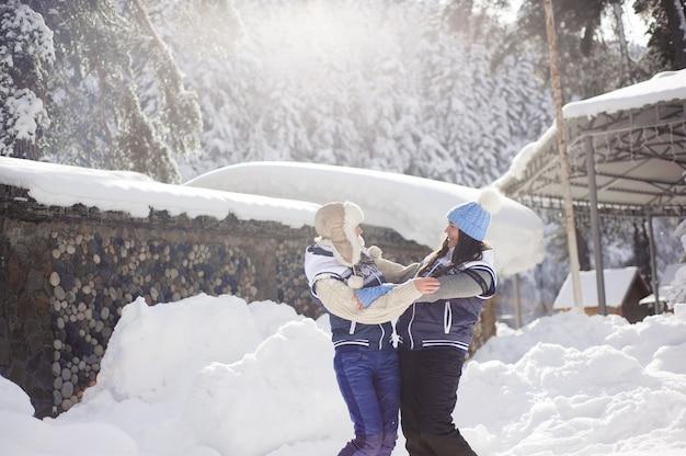 Duas amigas se divertem e desfrutam de neve fresca em um lindo dia de inverno