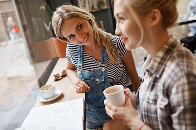 Duas amigas sentadas dentro de um café tomando café