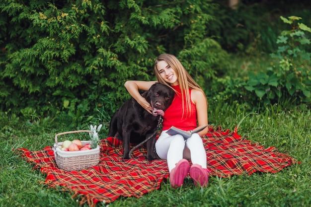 Duas amigas sentadas no cobertor acariciando no jardim, uma mulher loira e seu cachorro