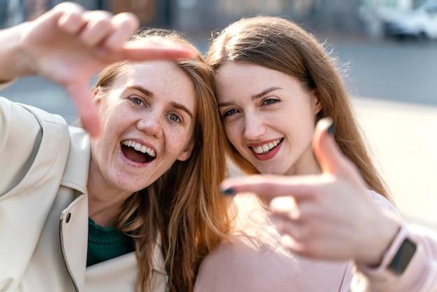 Duas amigas sorridentes ao ar livre na cidade fingindo tirar uma selfie