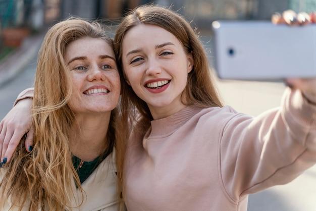 Duas amigas sorridentes ao ar livre na cidade tirando uma selfie