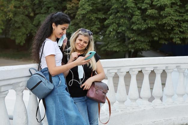 Duas amigas sorridentes estão perto do parque e ouvem música nos mesmos fones de ouvido