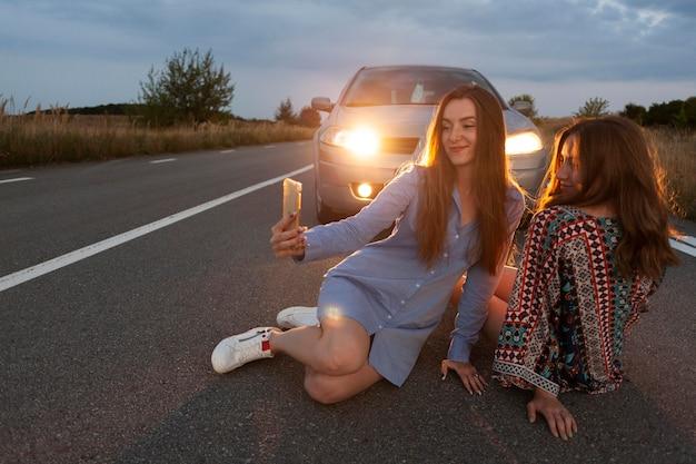 Duas amigas tirando uma selfie na frente do carro na estrada