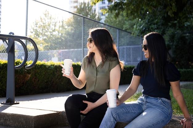 Duas amigas tomando uma xícara de café juntas no parque