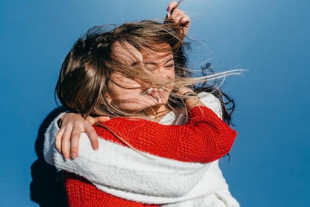 Duas amigas, uma loira e uma morena, se abraçando em um dia de vento forte sobre fundo azul