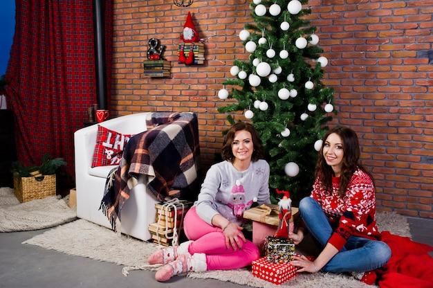 Duas amigas usam blusas de inverno, sentada na sala com decorações de natal.