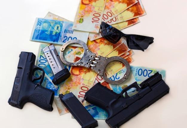 Duas armas, algemas, notas do novo shekel israelense, novas notas de 100, 200 nis, moeda com óculos de sol