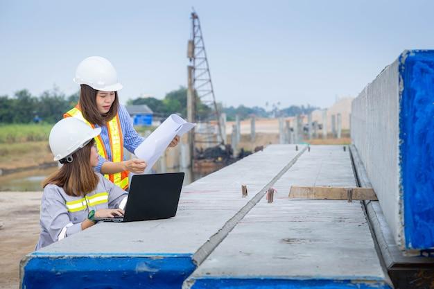 Duas arquitetas líderes trabalhando com laptop e projetos no canteiro de obras ou canteiro de obras