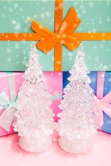 Duas árvores de natal de vidro branco com presentes com laços em um fundo rosa