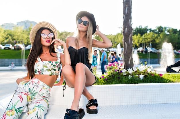 Duas atraentes garotas loiras e morenas com cabelos longos estão posando para a câmera no parque. eles usam roupas sensuais, chapéu e óculos escuros.