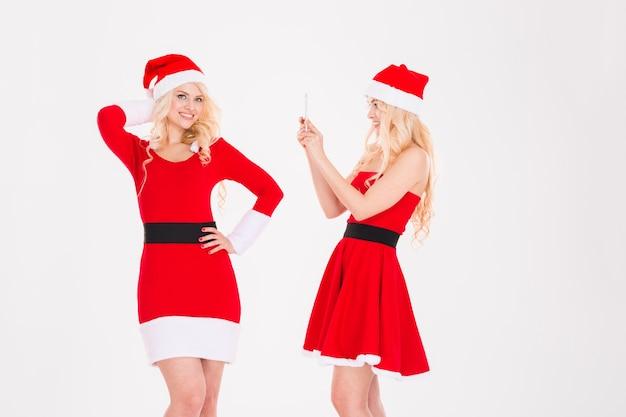 Duas atrativas jovens irmãs gêmeas em vestidos de papai noel vermelhos e chapéus mostrando um laptop com tela em branco perto da árvore de natal sobre fundo branco