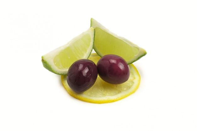Duas azeitonas e partes de limão e limão isoladas no fundo branco.