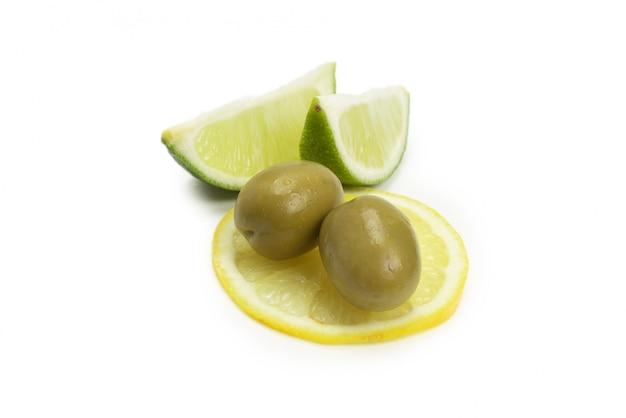 Duas azeitonas e um pedaço de limão e lima isolado no branco